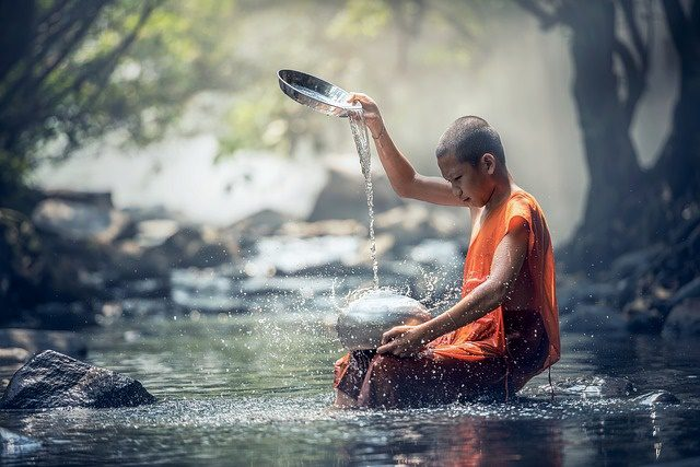 young monk sitting in river pouring water