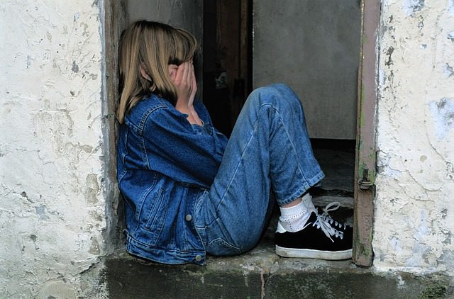 scared girl in jeans and sneakers sitting in the doorway with her face in her hands