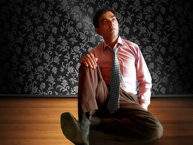 man sitting on the floor in a shirt and tie, pensively looking upward, taking a retreat