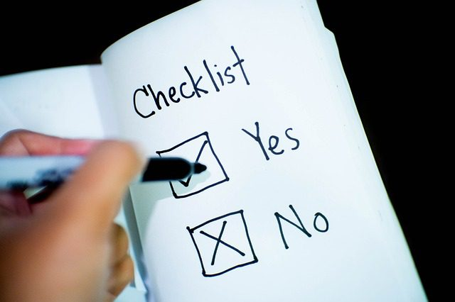 "Light brown-skinned left hand holding a marker, checking off ""yes"" and ""no"" boxes on a checklist."