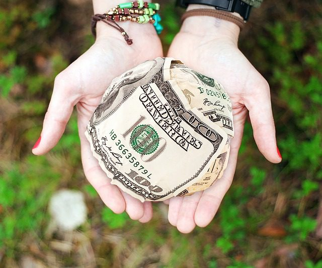 hands open offering a ball of hundred-dollar bills
