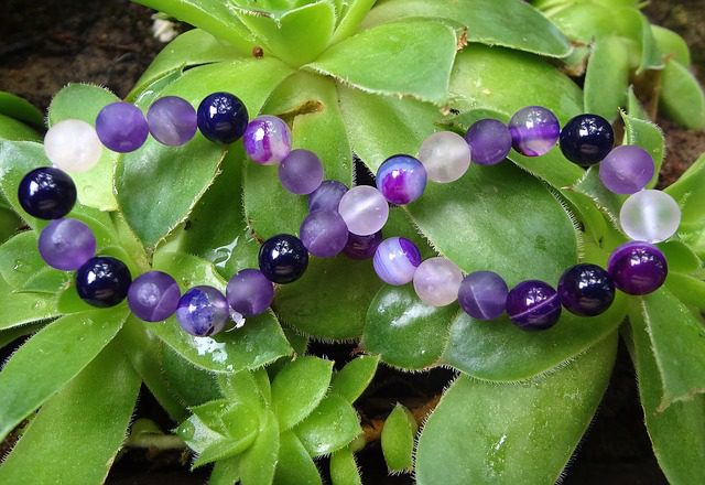 Amethyst-beaded bracelet resting on leaves of a succulent-type plant