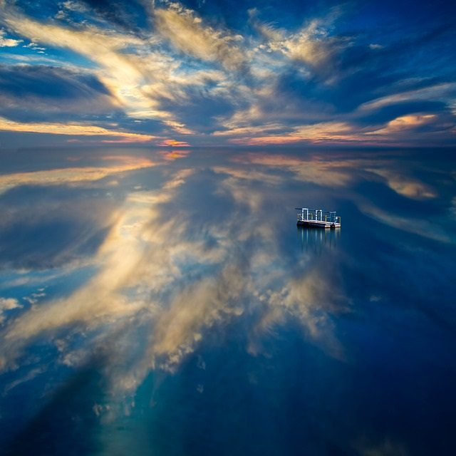 small sturdy raft on an ocean reflecting the sky
