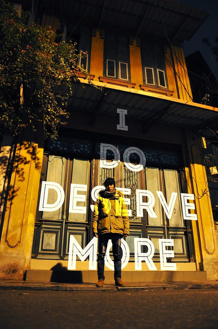 "A colonial-style house in Hanoi with the words ""I Do Deserve More"" projected onto the facade as well as th eperson standing in front of it ewaring a jacket, jeans, and a hat, yellow-orange overtones."