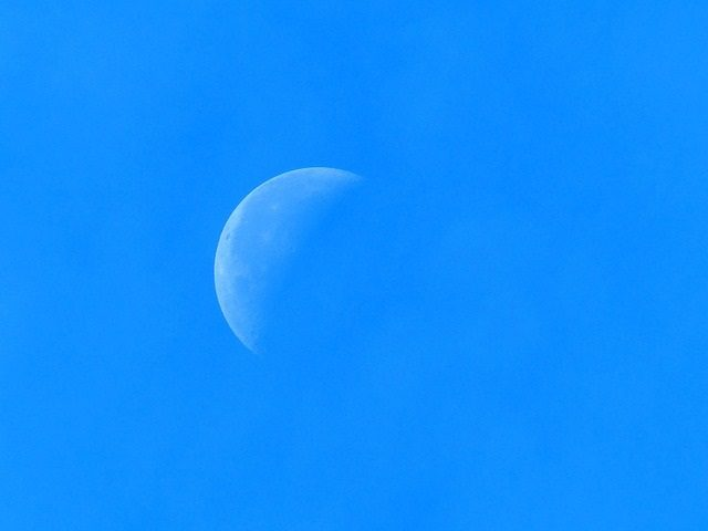 a pale half-moon on a turquoise background