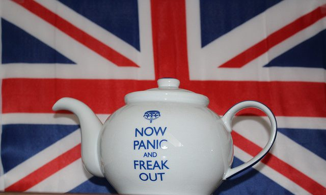 "White teapot with ""Now Panic and Freak Out"" printed in blue, against a background of the flag of the United Kingdom."