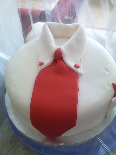 round cake that looks like a button-down shirt with a red tie down its center