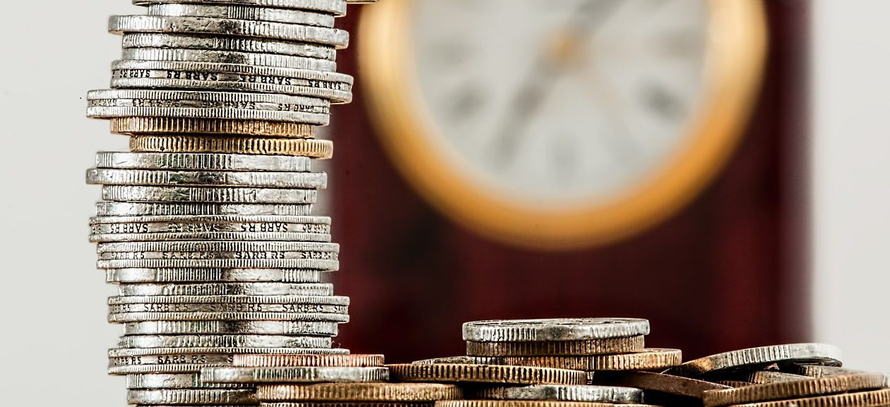 A close-up of a pile of coins in front of a clock that is blurred in the background.