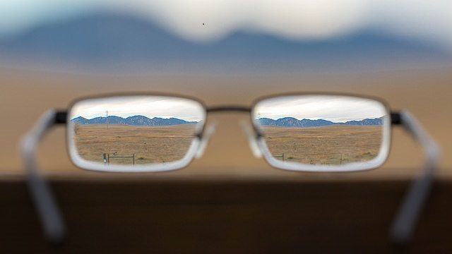 Background of blurry mountains and fields with a pair of glasses through which you see the mountains and fields clearly.