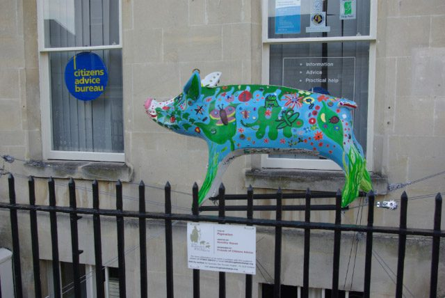 Citizen's Advice Bureau sign in the United Kingdom with a brightly colored pig sculpture in front of it.