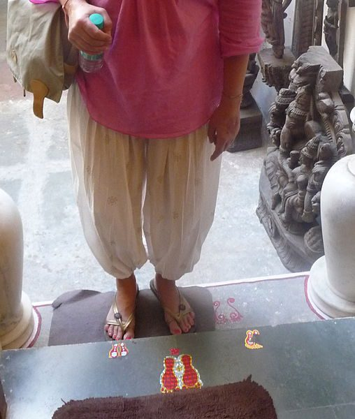 A person standing at what looks like an Indian temple on steps which bear stickers of footprints.