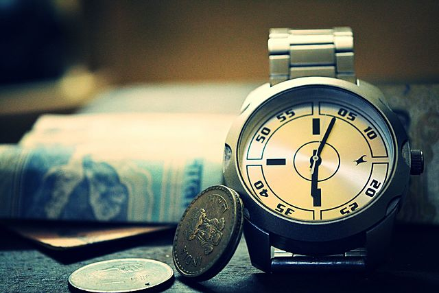 A wristwatch, coins and folding money.