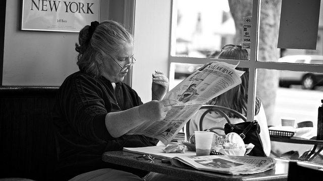 black and white image of a woman reading the newspaper in the window of a restaurant