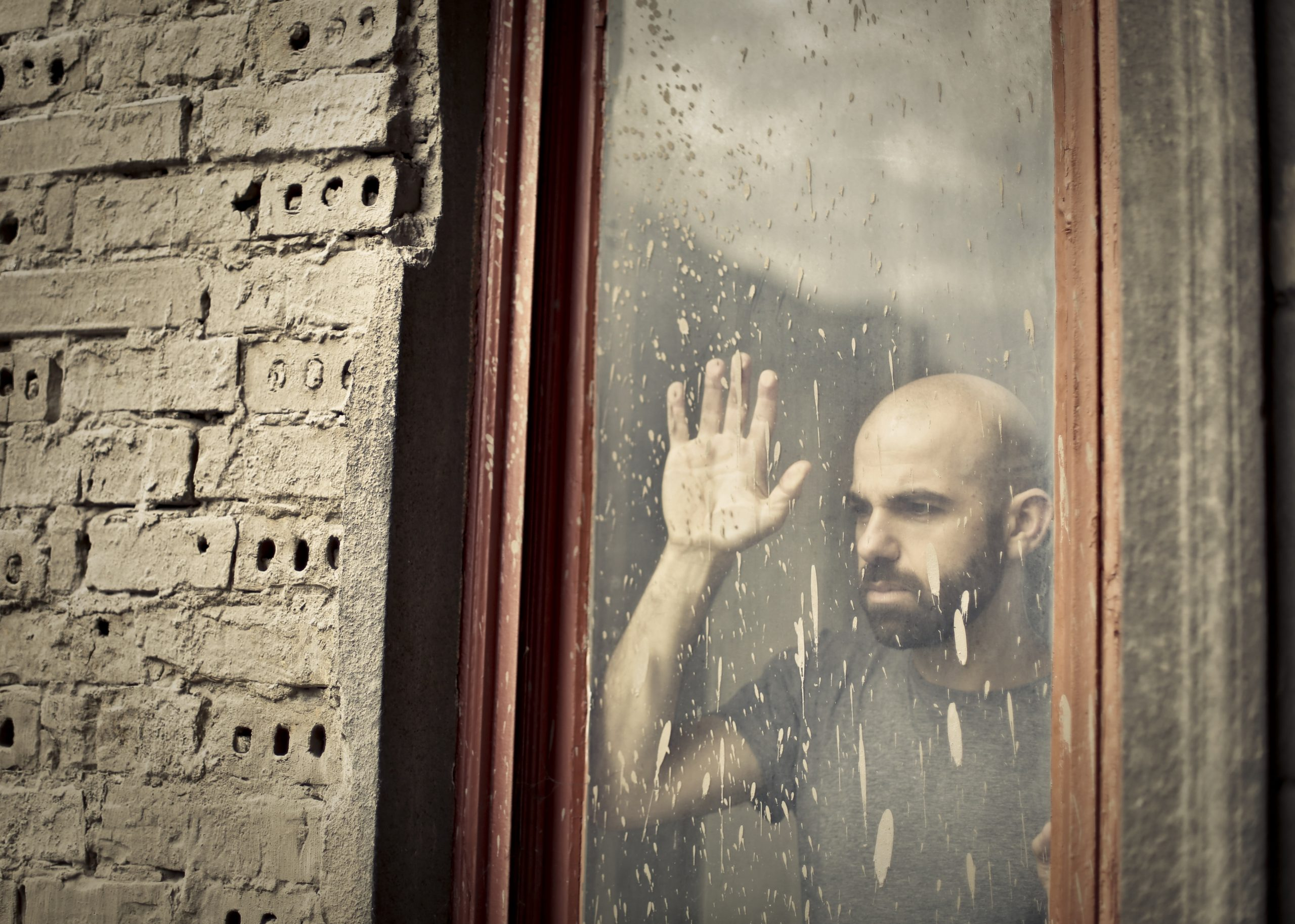 bearded, light-skinned person with hand against window, looking quietly desperately out onto rain